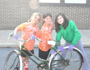 From left, Samantha Scott, Jordan Hower and Meghan Berry, all of East Marlborough, work to clean up a donated bike. Dozens of kids and adults gathered Saturday to work on the donated bikes at Patton Middle School.